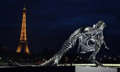 """Soaring over the seine river in Paris sits a life-size Tyrannosaurus-Rex sculpture, conceived and constructed by french artist Philippe Pasqua."""